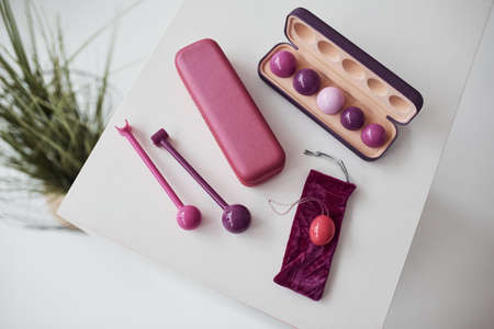 Close up view of pink vaginal balls and stimulators lying down on the table. Conception of imbuilding and woman health.