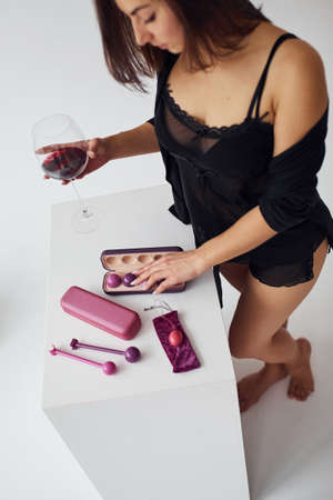 Woman in black clothes, with vaginal balls and imbuilding tools in the room.