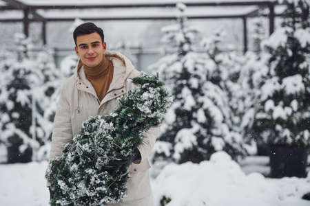 Young handsome man carrying fresh cutted fir tree outdoors.