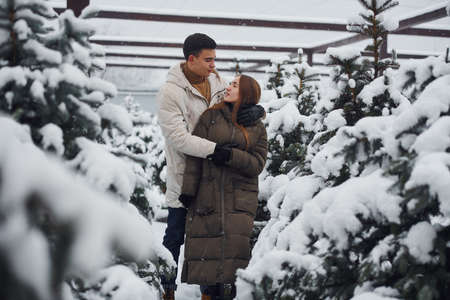 Young cute couple walking outdoors near fresh christmas fir trees. Stock fotó