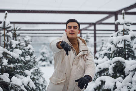 Cheerful young guy throwing snowballs outdoors near fir trees.