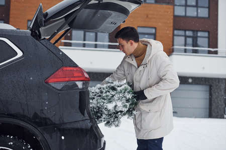 Man in white coat putting christmas fir tree inside his automobile.