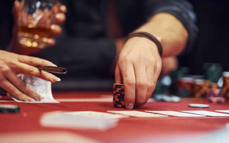 Close up view of elegant young peoples hands that playing poker in casino.