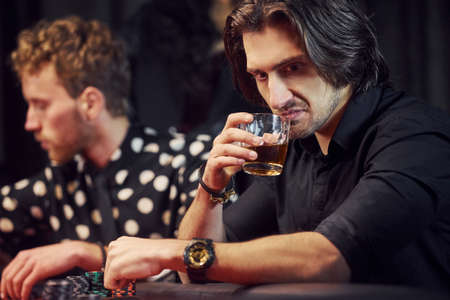 Man with drink feels bad and scared. Elegant young people sits by table and playing poker in casino.