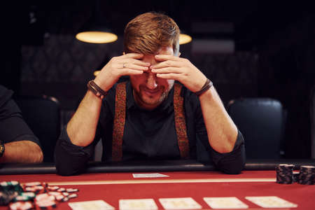 Elegant young man sits in casino and feels bad because loses poker game.