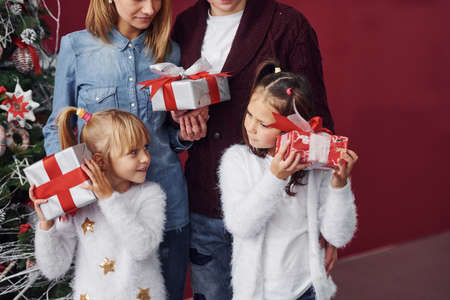 Two little girls stands together with mom and dad in room with christmas tree with gift boxes. 免版税图像 - 158000403