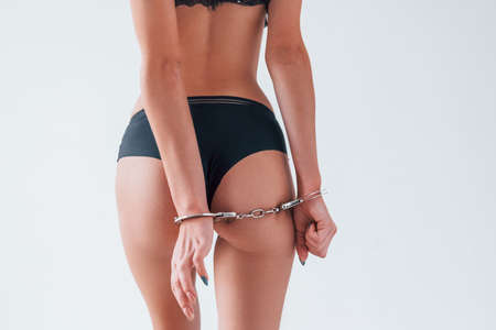Hot sexy woman with handcuffs is in the studio. Conception of intimacy.