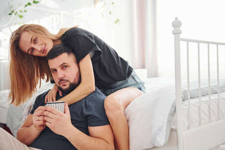 Young married couple with cup of drink have leisure together in bedroom at daytime. Banque d'images