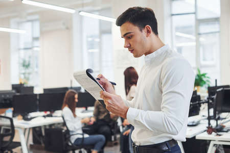 Man in formal wear standing with notepad in hands indoors in office with young people that works behind him.