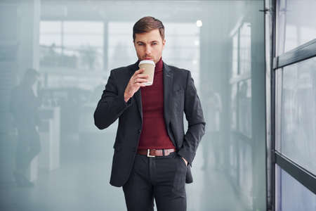 Young business man in luxury suit and formal clothes wth cup of drink is indoors in the office.
