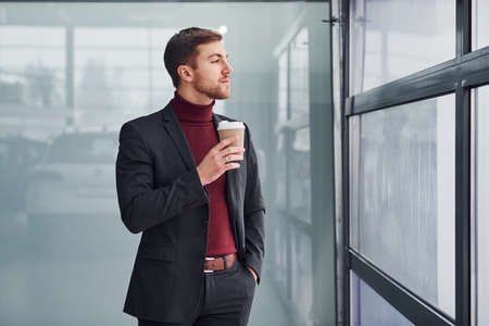 Young business man in luxury suit and formal clothes wth cup of drink is indoors in the office. Imagens