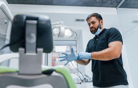 Portrait of dentist in gloves that standing indoors in the clinic.