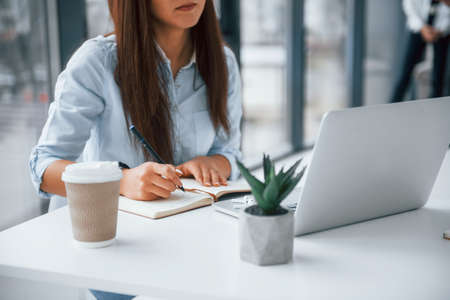 Woman with laptop sitting in front of group of young successful team that working and communicating together indoors in office.