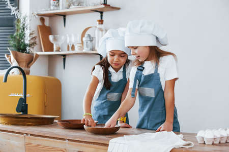 Two little girls in blue chef uniform working with flour on the kitchen.