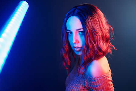 Portrait of young girl with curly hair that holds lighting sticks in red and blue neon in studio.