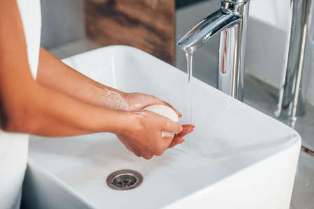 Close up view of woman that washing her hands by using soap.