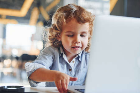 Smart child in casual clothes using laptop for education purposes or fun.