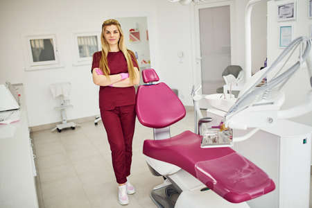 Young female dentist in uniform standing in stomatology office. Stock Photo