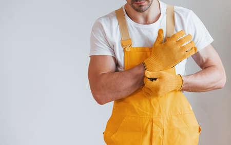Handyman in yellow uniform preparing for work indoors. House renovation concept. Imagens