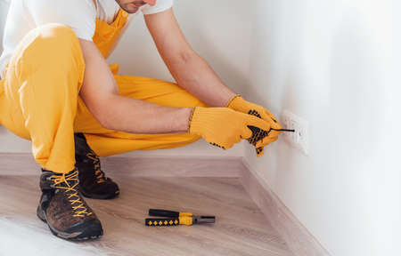 Handyman in yellow uniform works with electricity and installing new socket. House renovation conception.
