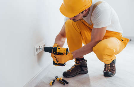 Handyman in yellow uniform works with electricity and installing new socket by using automatic screwdriver. House renovation conception.