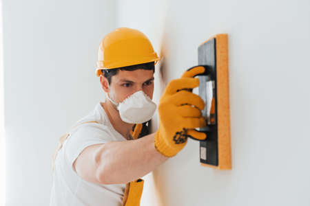 Handyman in yellow uniform and protective mask polishing wall indoors. House renovation conception. Imagens
