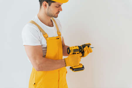 Handyman in yellow uniform standing against white wall with automatic screwdriver. House renovation conception.