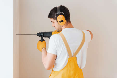 Handyman in yellow uniform works indoors by using hammer drill. House renovation conception. Imagens