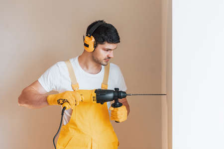 Handyman in yellow uniform works indoors by using hammer drill. House renovation conception.