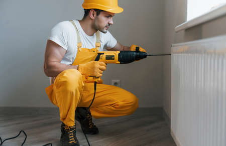 Handyman in yellow uniform works with drill indoors. House renovation conception.