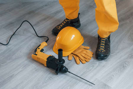 Handyman in yellow uniform with drill standing indoors. House renovation conception.