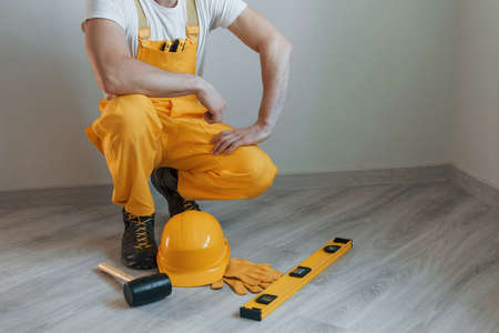 Tools on the floor. Handyman in yellow uniform standing indoors. House renovation conception.