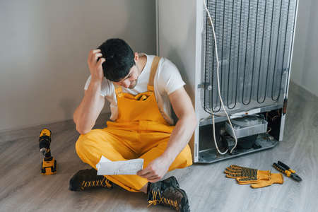 Confused handyman in yellow uniform reading manual for fridge indoors. House renovation conception. Imagens