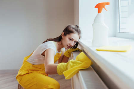 Housewife in yellow uniform works with window and surface cleaner indoors. House renovation conception. Imagens