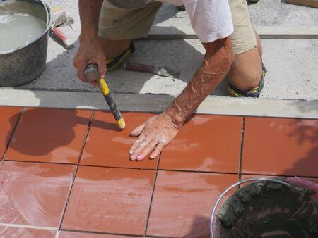 worker tiler metre laying tiles intent in his work