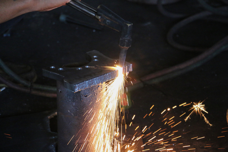 The men are welding and decorating the iron, using the heat energy with a beautiful light.