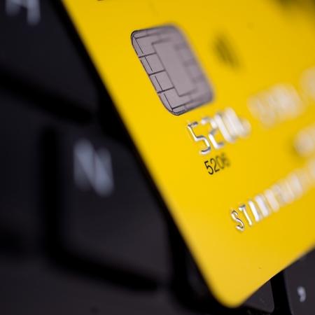 yellow credit card on black keyboard background photo
