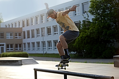 Unknown young adult rides on a skateboard plaza