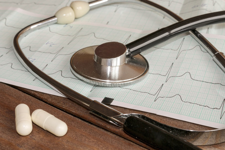 pharmacologist: The concept of insurance or a healthy lifestyle. Medical stethoscope head lying on the graph of a cardiogram with pills closeup on wooden background. Cardiac care, health, prevention and care.