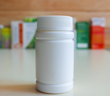 airtight: Jar with airtight lid for storing pills and ointments.Drugs in the blur in the background.