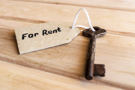 The concept of real estate for rent old key with a tag on wooden background.