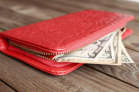 economise: Female red wallet with money on a dark wooden background.The concept of cost of money. Stock Photo