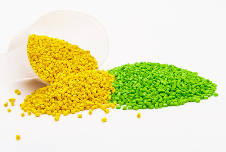 Green and yellow plastic pellets scattered from the measuring Cup on a white background. Polymeric dye for plastics.