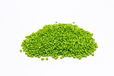 Green plastic pellets on a white background. Polymeric dye for plastics. Stock Photo