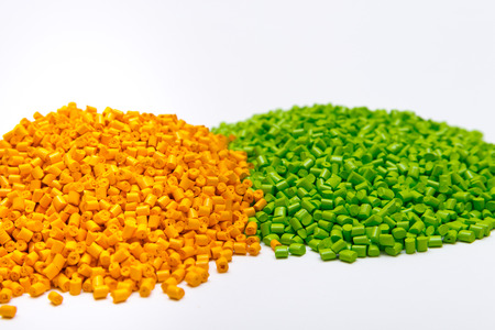 Green and orange plastic pellets on a white background. Polymeric dye for plastics.