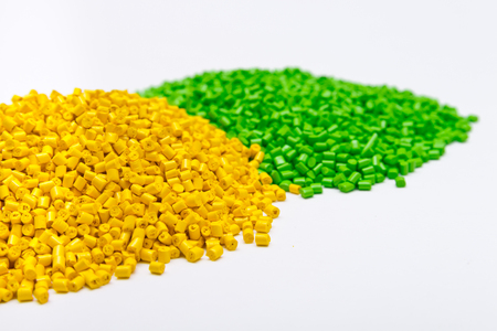 Green and yellow plastic pellets on a white background. Polymeric dye for plastics.