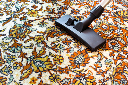 Cleaning old carpet with a vacuum cleaner with a black nozzle . Stock Photo