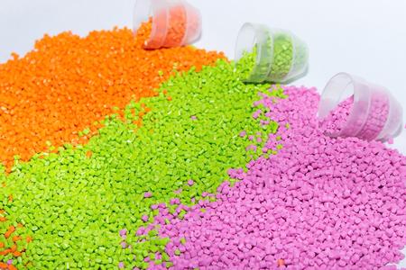 Los gránulos de plástico. Colorante polimérico naranja, verde y rosa. Tinte para plásticos en gránulos. Foto de archivo - 78206801