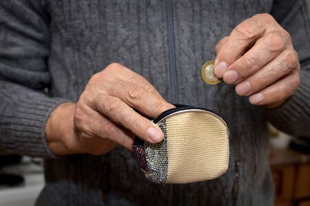 billfold: An elderly man in a hand holds a coin and a empty wallet. The concept of poverty in retirement.