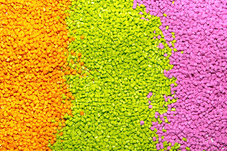 The plastic granules. Polymeric dye orange, green and pink . Dye for plastics in granules . Stock Photo